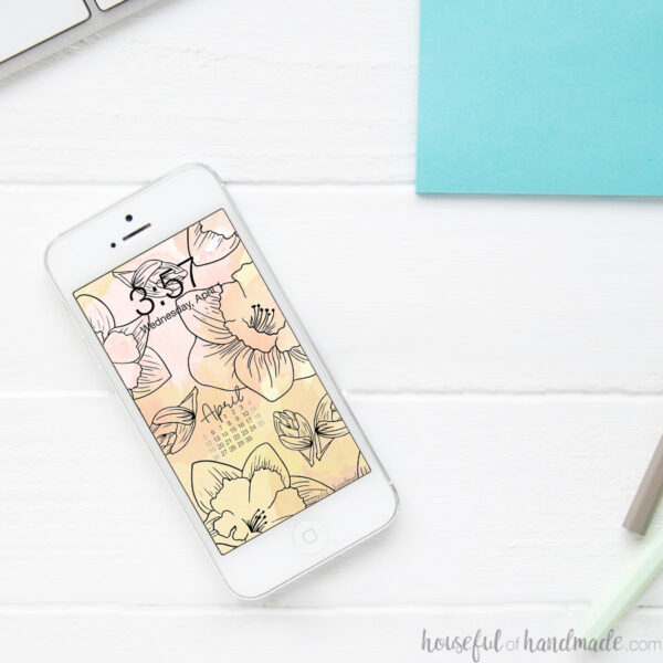 Smartphone sitting on a white desk with free digital wallpaper on the screen.