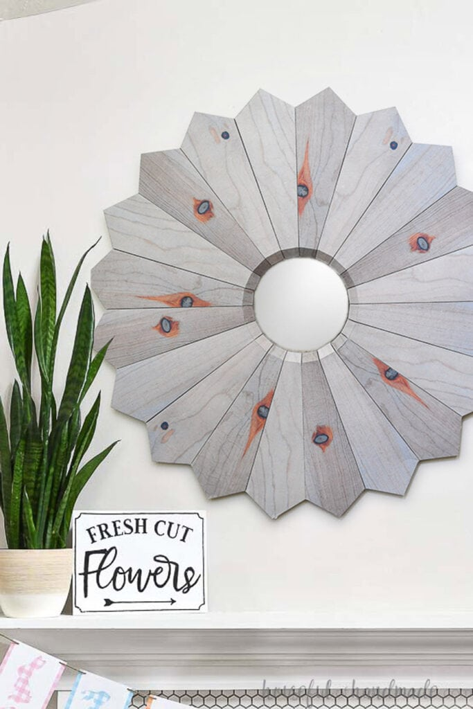 Wood sunburst mirror on the wall above the mantel that is made out of paper.
