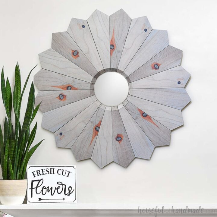 Square photo of the aged wood sunburst mirror hanging next to a plant and fresh cut flowers plaque.
