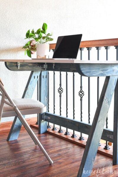 DIY fold-away desk with navy blue legs and a white desk top.