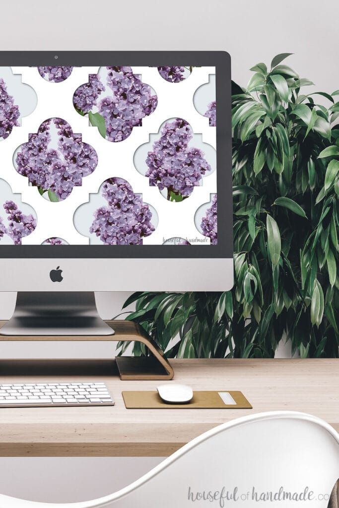 White lattice pattern with lilacs peeking through as a digital wallpaper on a computer screen.