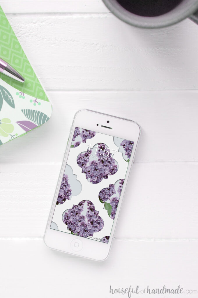 Smartphone with the lilac digital wallpaper on the home screen.