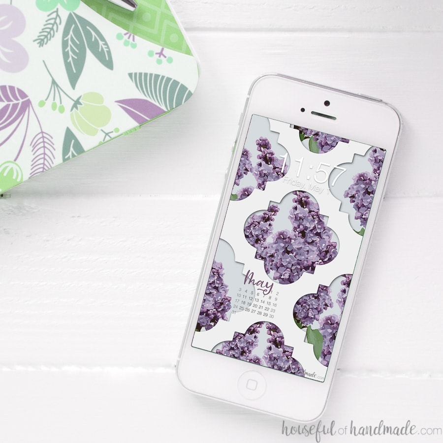 Lilac design digital wallpaper on the background of a white iPhone sitting on a table.