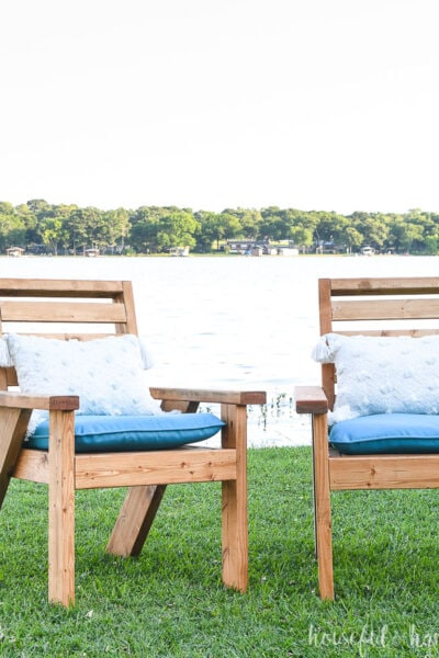 Two outdoor lounge chairs with cushions o the lawn.