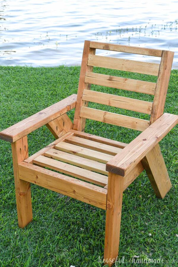 Outdoor chair on the grass with no cushions on it.