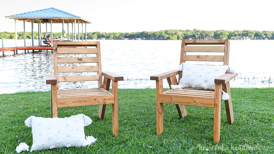 Two DIY outdoor chairs with pillows in front of a lake.