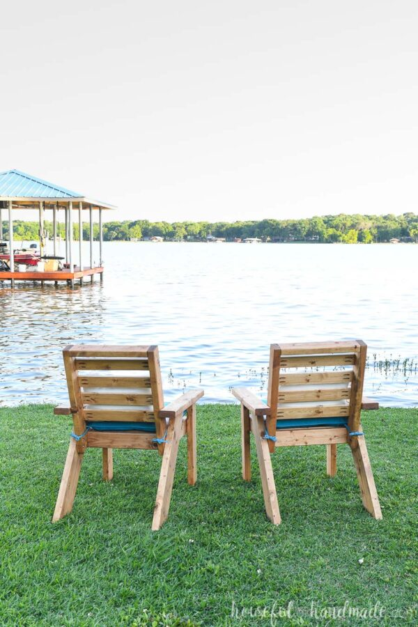 The back of the two outdoor chairs as they are looking over the lake.