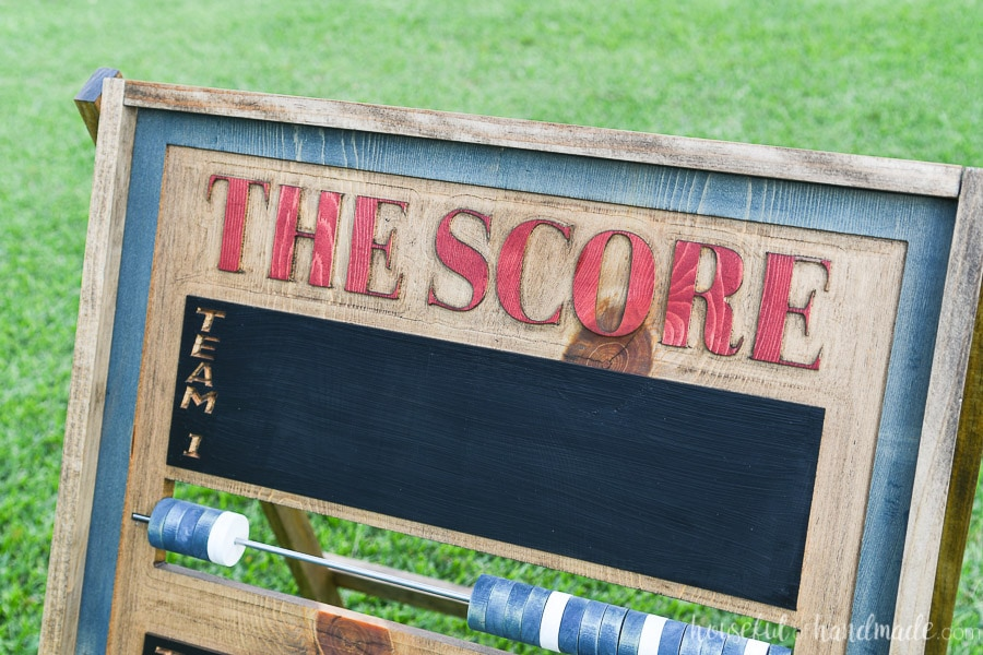 "Close up shot of the carved words ""The Score"" on the top of the score keeper board."