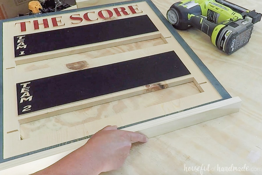 Nailing the frame to the bottom of the scoreboard.