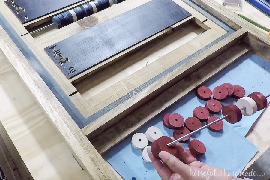 Threading stained beads on the metal rod before glueing into the scoreboard.