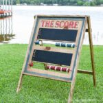 Square photo of the carved scoreboard with red and blue wood beads sitting on the grass.