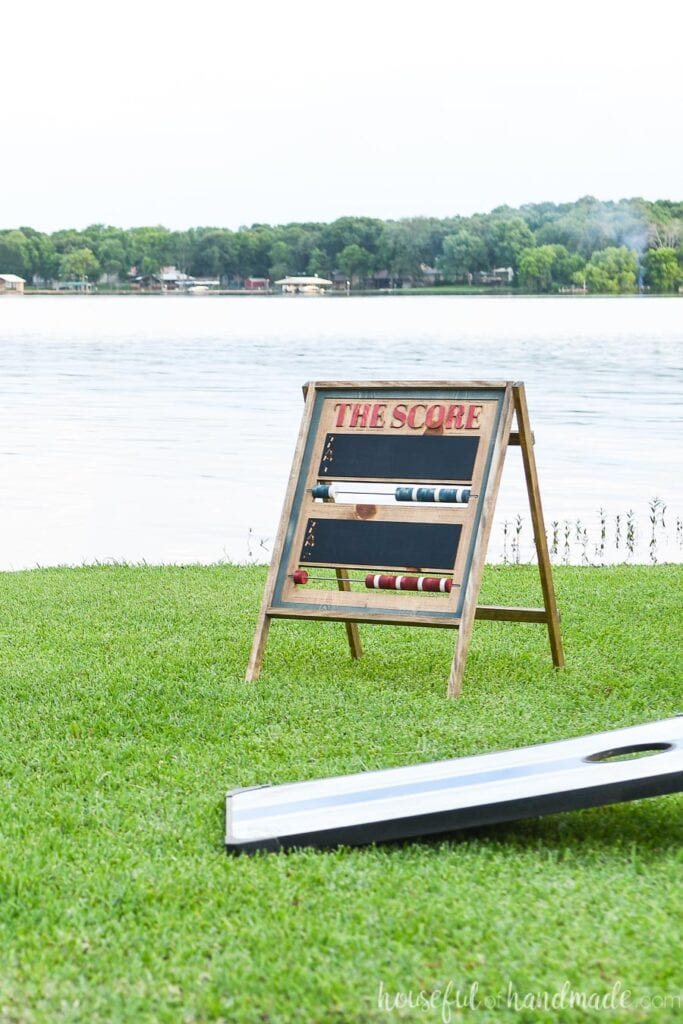 DIY scoreboard on the lawn in front of the lake with corn hole board in front of it.