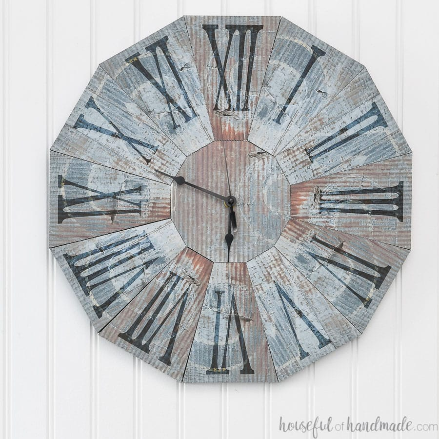 Wall clock that looks like rustic blue steel clock made from paper.