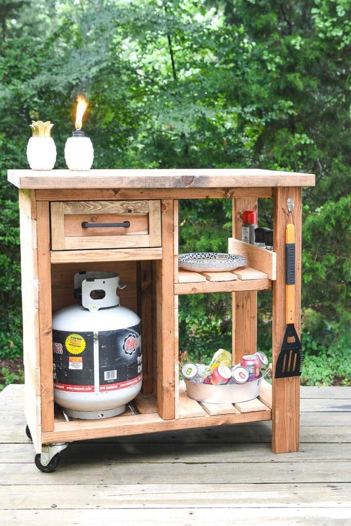 Outdoor grill table on wheels with cedar slats on the sides and on the shelves.