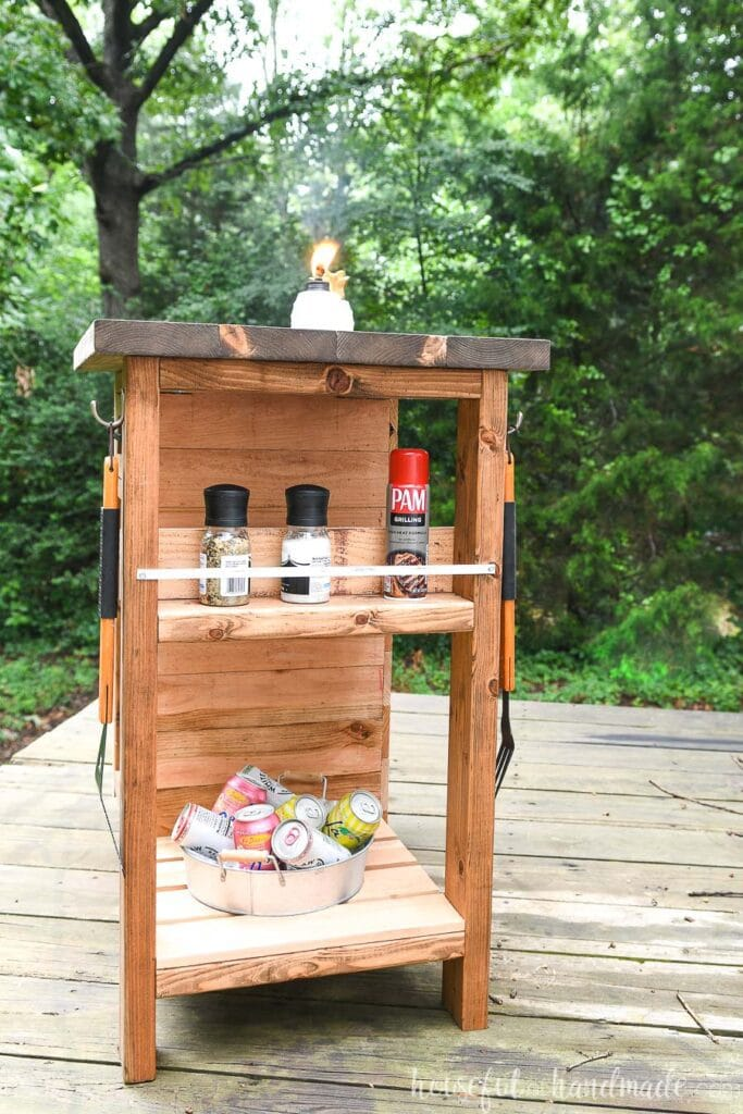 Grill cart with spice rack on the end holding salt & pepper grinders and gilling spray, bottom shelf with drinks in a bucket.