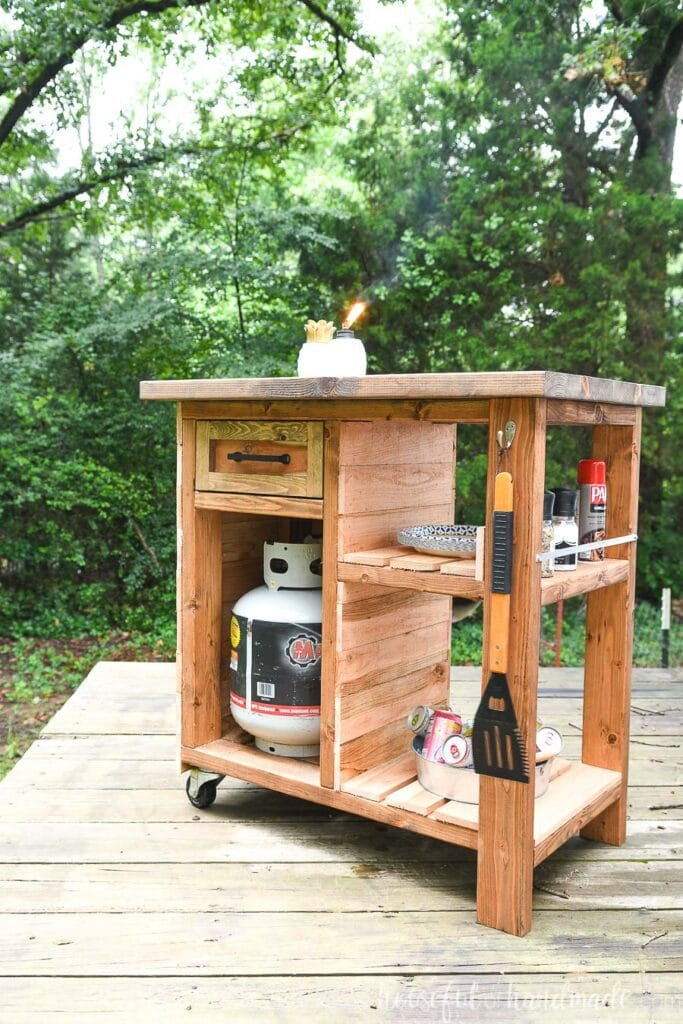Cedar clad rolling grill cart with storage sitting on a deck in front of trees.