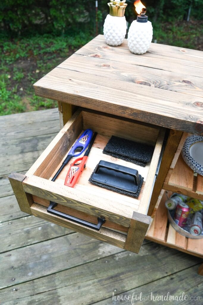 Close-up of the drawer on the grill table open with grill accessories inside.