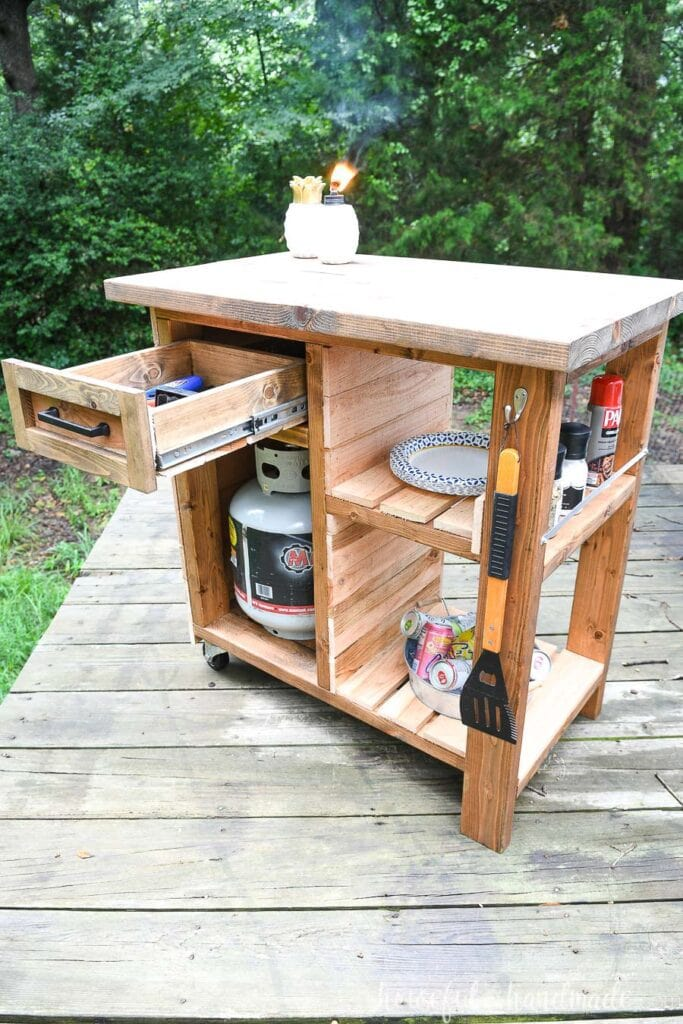 DIY grill cart with drawer (open in picture) extra fuel tank storage, and shelves for storage.