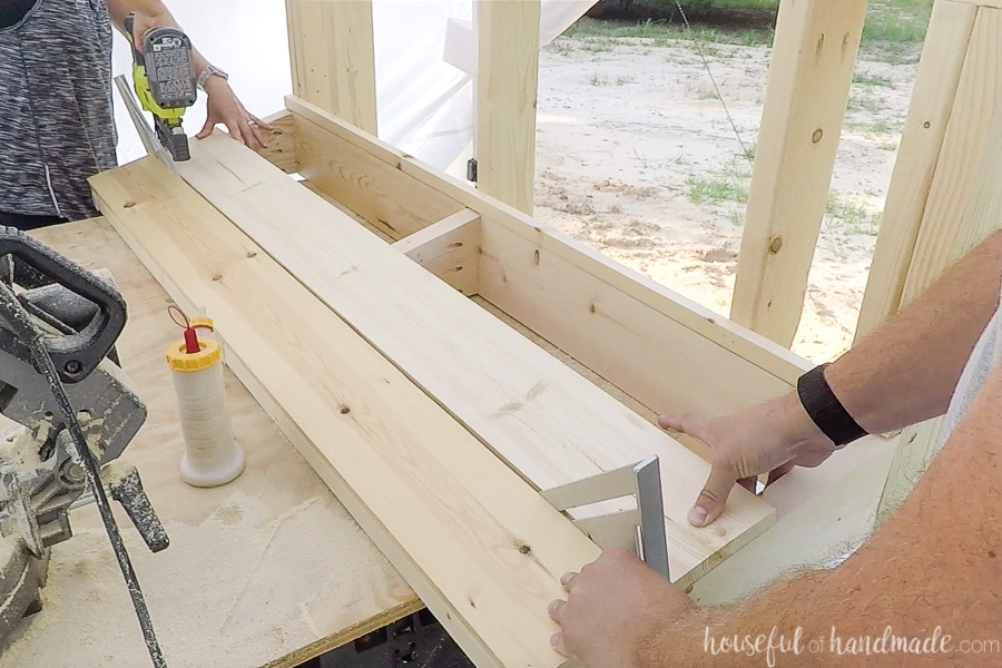 Attaching the 1x6 slats for the back rest with nails and spacing them with speed squares.