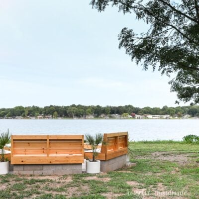 Overlooking the lake with a fire pit made from cinderblocks and wood close to the shore in the landscape.