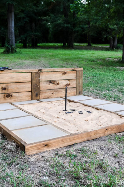 DIY Horseshoe pit with sturdy backstop and throwing platforms with concrete pavers.
