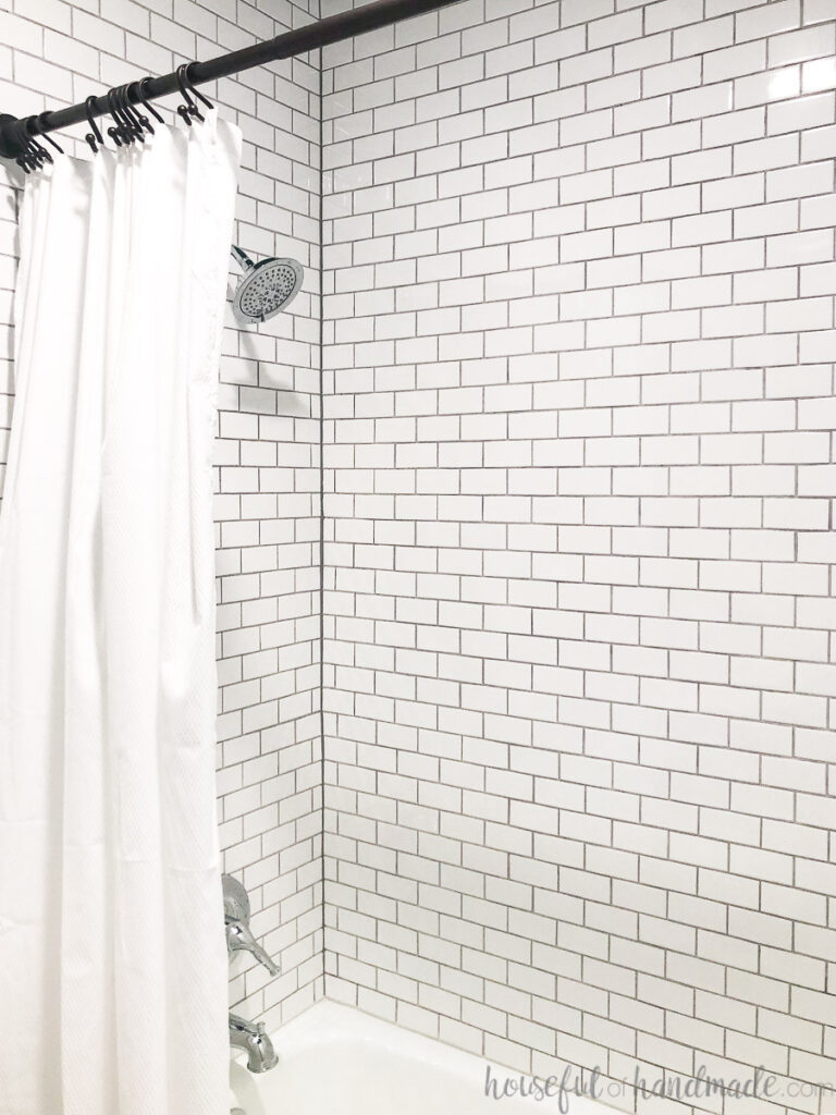 Bathtub and surround tiled with small subway tiles in white.