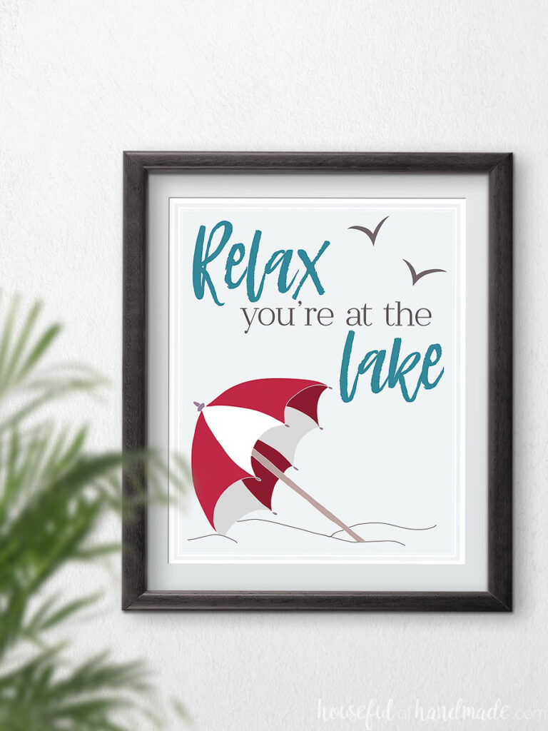 "Red beach umbrella art with text ""relax your at the lake"" in a frame."