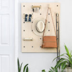 Entryway organizer made from plywood hanging on the wall next to a door.