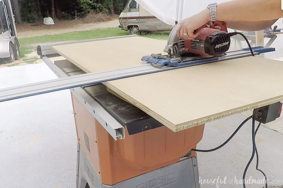 Cutting a piece of plywood with a circular saw and guide track.