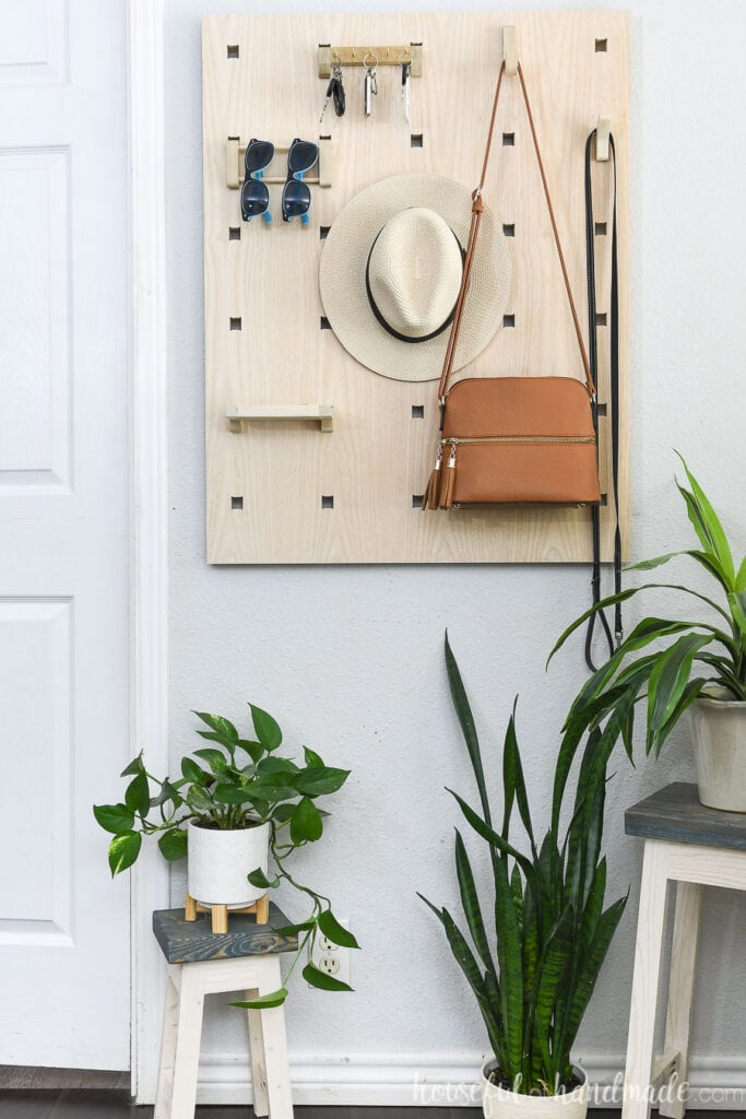 Straight on picture of the modular entryway organizer with a purse, hat, sunglasses and keys hanging on it.