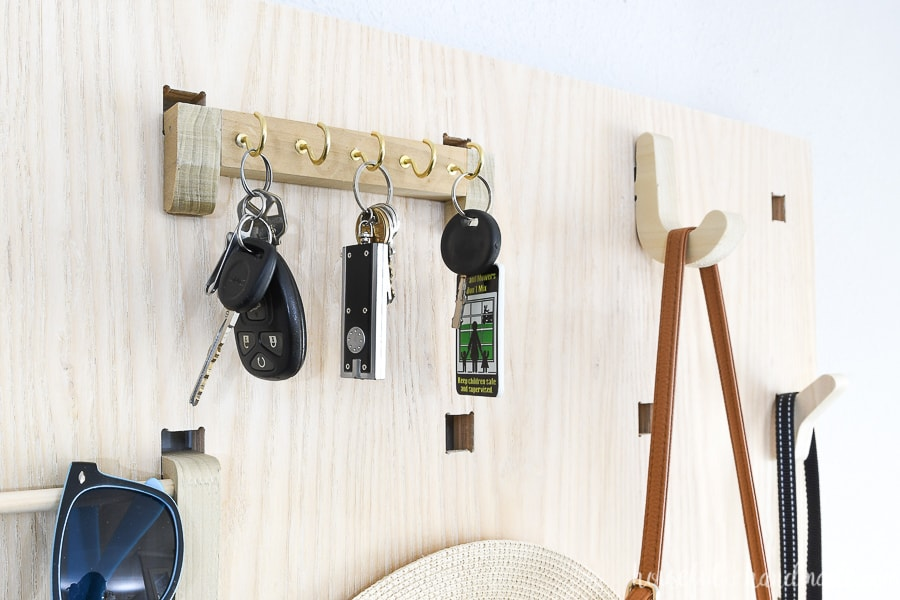 Close up picture of the key holder component holding 3 sets of keys on the 5 key hooks.