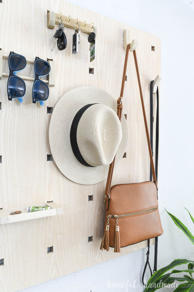 Close up view of the entryway wall organizer with purse, hat and more hanging on it.