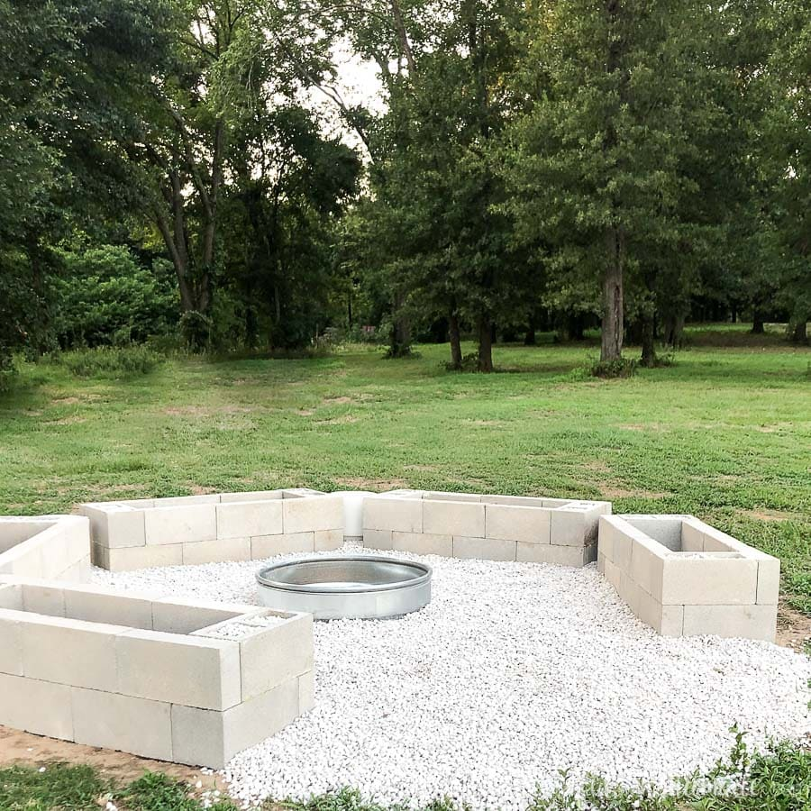 DIY fire pit area with stacked cinder blocks surrounding a metal fire ring and limestone pebbles between them.