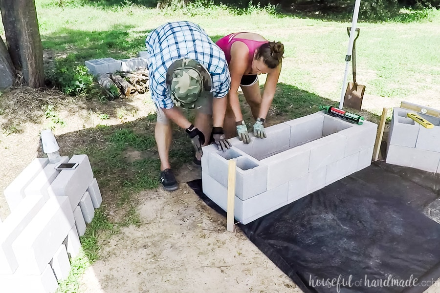 Finishing assembling the bases of concrete blocks for the DIY fire pit area.