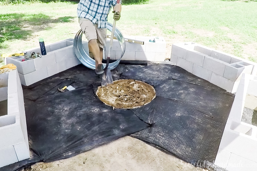 Digging out a hole in the center of the fire pit area to put the fire ring into.