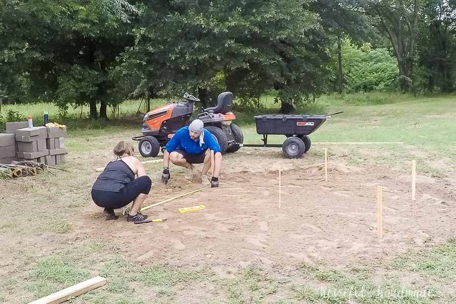Restaking the hexagon in the ground to start laying the cinder block seating bases.