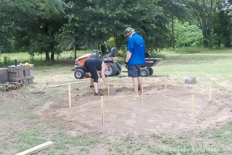 Leveling the first cinder block for the fire pit seating area.