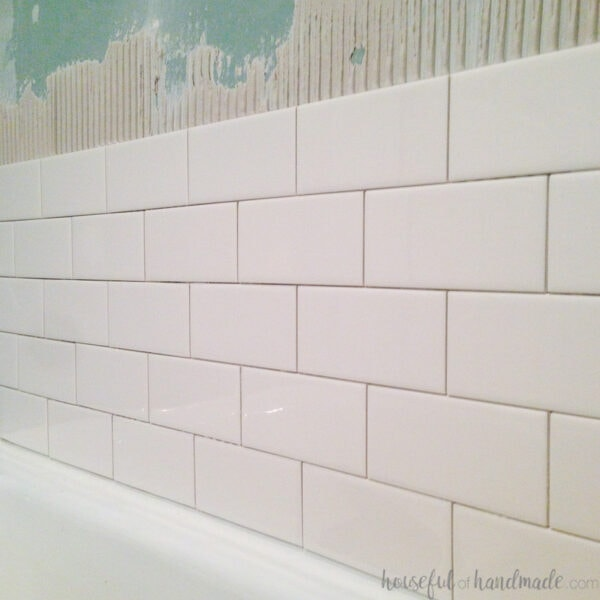 Five rows of white subway tiles starting to be installed above a bathtub.