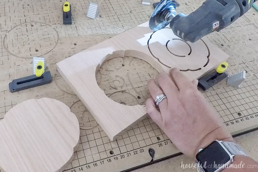 Removing the carved pieces from the wood with a saw.