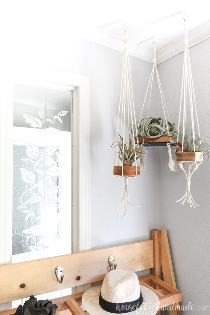 Corner of the house with 3 air plants hanging on wood and macrame air plant holders.
