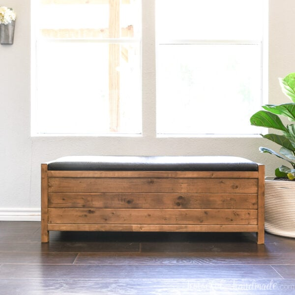 DIY storage bench with upholstered top and large storage compartment in front of a window.