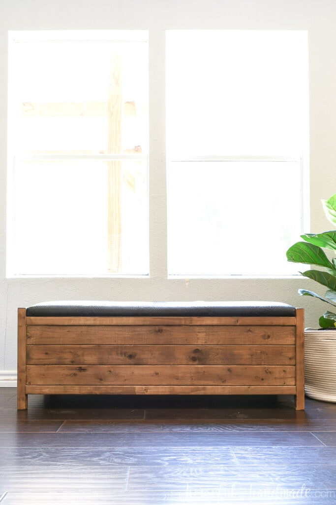 Front view of the simple wood storage bench with black leather top that lifts up.