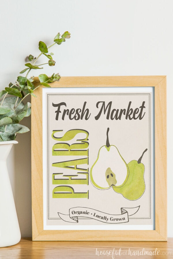 Fresh market pears farmers market sign in a frame next to a vase.