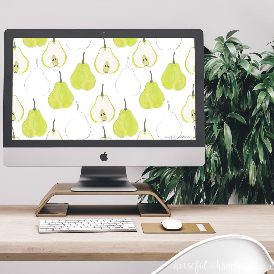 Green pear digital wallpaper as the background on an iMac computer on a desk.