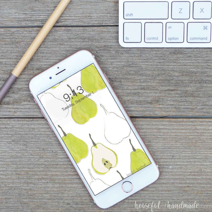 White smartphone with watercolor pear digital background on the screen sitting on a reclaimed wood desk top.