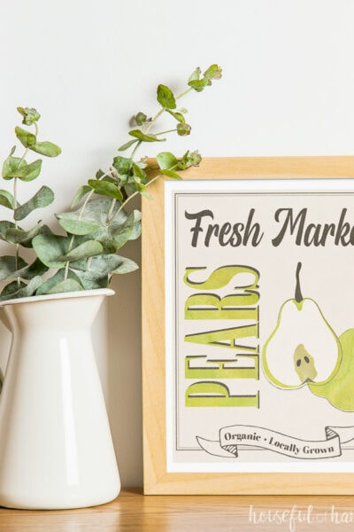 White vase with eucalyptus leaves next to maple frames with fall printable art in it, designed around a watercolor pear.