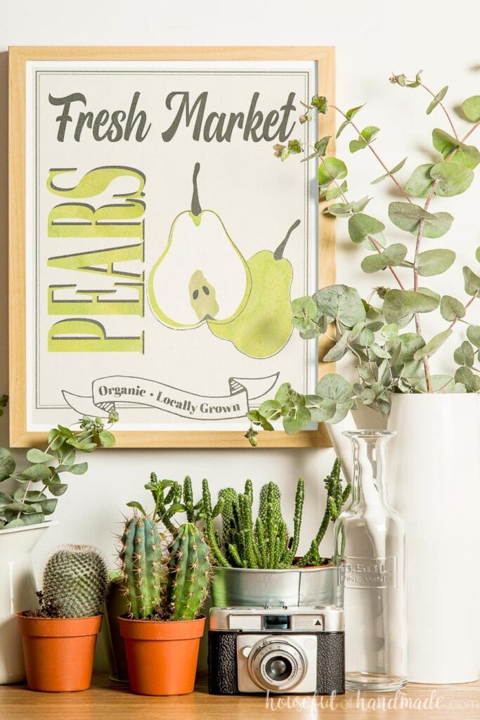 Fall vignette with printable farmers market sign surrounded by plants in pots and vases.