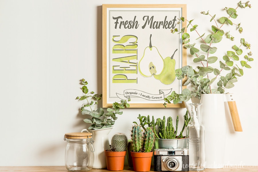 Console table decorated with planted cactus, vases with eucalyptus and a pear fall printable in a frame on the wall.