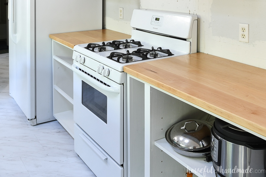 White cabinets carcasses installed around white range with light colored wood countertops on them.
