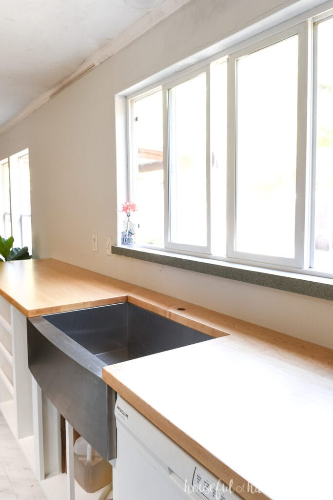 DIY wood countertops made from hard maple on top of white kitchen cabinets with a stainless steel farmhouse sink and large window in the wall above.